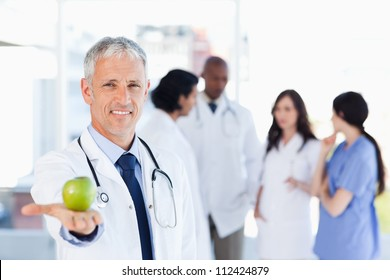 Smiling doctor holding a green apple in his right hand