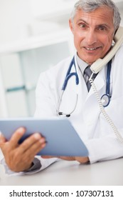 Smiling doctor holding a tablet computer and calling in medical office
