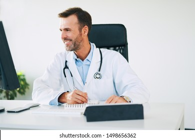 Smiling doctor looking at computer screen while writing in calendar