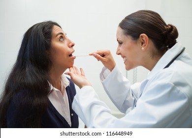 Smiling doctor looking into patients mouth in hospital room