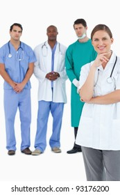Smiling doctor with male staff members behind her against a white background