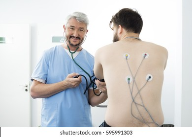 Smiling Doctor Measuring Blood Pressure Of Patient In Hospital