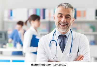 Hymyilevä lääkäri poseeraa kädet ristissä toimistossa, hänellä on stetoskooppi, hoitohenkilökunta taustalla