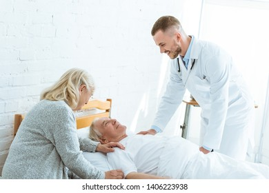 smiling doctor and senior woman near ill patient in clinic