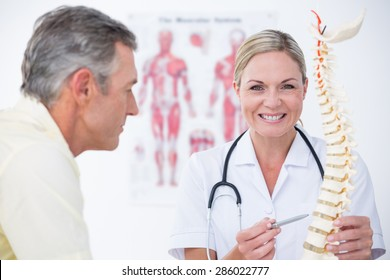 Smiling doctor showing her patient a spine model in medical office