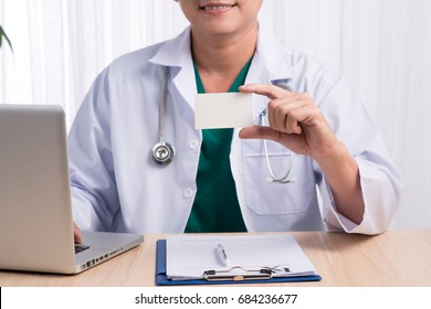 Smiling doctor sitting at his desk in medical office showing namecard