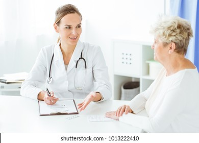 Smiling doctor with stethoscope and sick woman during dietician consultation