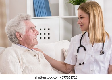 Smiling doctor supporting her patient and holding his sholuder