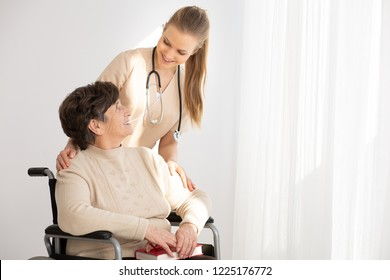 Smiling doctor supporting sick elderly woman in the wheelchair next to copy space