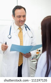 Smiling doctor talking to his patient in an examination room