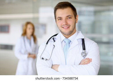 Smiling doctor waiting for his team while standing upright