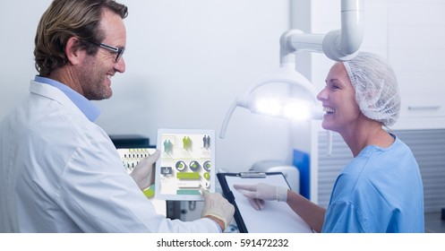 Smiling doctors discussing over digital tablet and clipboard in clinic
