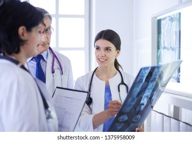 Smiling doctors discussing patient's diagnosis looking at x-rays in a hospital