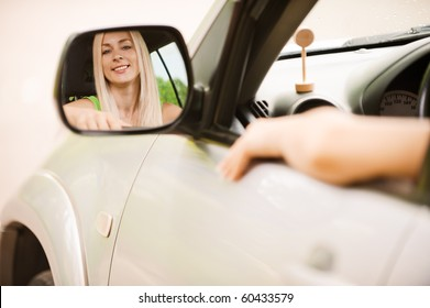 Smiling driver-woman is reflected in mirror of car.