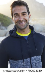 Smiling dude on beach in hooded top, portrait