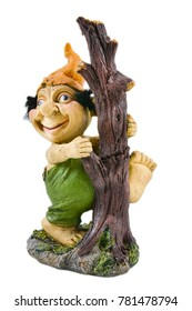 Smiling, the dwarf in the hat and green shorts stands near a tree on an isolated background. Plaster doll