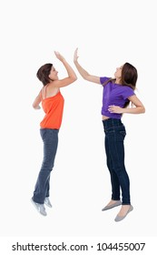 Smiling and dynamic teenagers jumping while giving a high-five