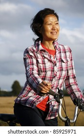 Smiling East Asian Woman Cycling in Richmond Park at Dusk