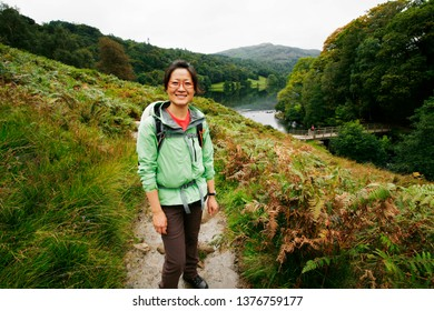 Smiling East Asian Woman hiking in Lake District, Cumbria, UK. Grasmere lake in the back ground.