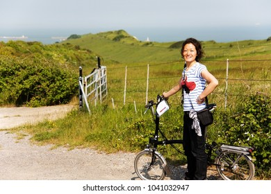 Smiling East Asian Woman in holiday cycling along the unpaved cycle route at seaside, Dover, UK.