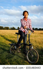 Smiling East Asian Woman in the park cycling at dusk, reed field and blue sky in the background.