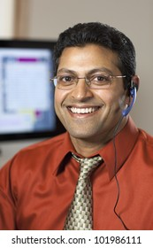 Smiling East Indian customer service representative with headset and computer monitor