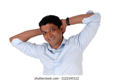 A smiling East Indian man in closeup standing in a blue shirt with his