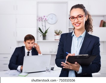 Smiling efficient business female secretary having cardboard in hands and working in office