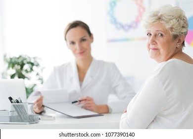 Smiling, elder dietician's patient sitting in her office and taking doctor's advice
