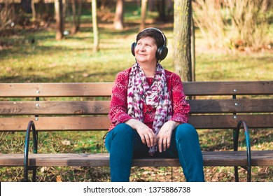 Smiling elder lady sitting on a bench in the park listening to music on her black headphones – Cute old lady relaxing and daydreaming in the park on a warm bright day