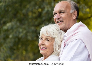 Smiling elder marriage relaxing in city park
