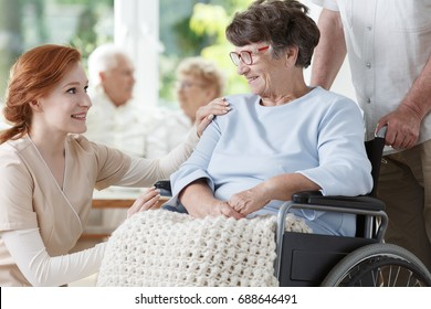 Smiling elder woman on wheelchair thanks young nurse for care