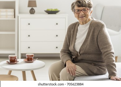 Smiling elder woman sitting next to coffee table with two red cups in white room