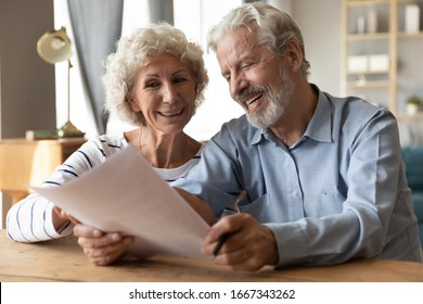 Smiling elderly 50s husband and wife sit at table in living room read contract agreement satisfied with terms and rules, happy old 60s couple customers or clients glad with pension health insurance
