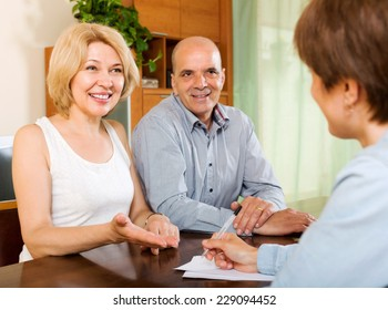 Smiling  elderly  couple discussing details of private insurance with agent