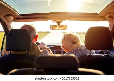 Smiling elderly couple driving car.
