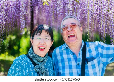 Smiling elderly couple in front of Japanese wisteria flowers