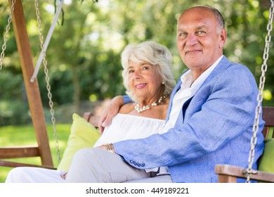 Smiling elderly couple spending time together on porch swing