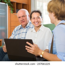 Smiling elderly couple talking with social worker with laptop at home. Focus on woman