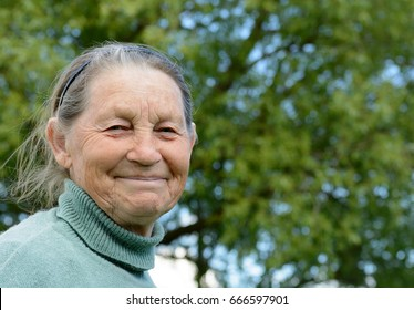 Smiling elderly grandmother. Russian old woman in the village