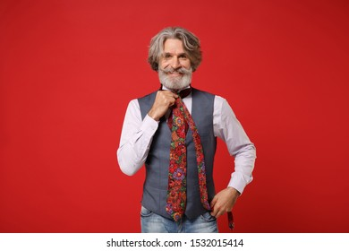 Smiling elderly gray-haired mustache bearded man in classic shirt, vest posing isolated on red wall background studio portrait. People lifestyle concept. Mock up copy space. Trying on colorful tie