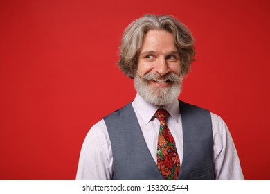 Smiling elderly gray-haired mustache bearded man in classic shirt vest and colorful tie posing isolated on red background, studio portrait. People lifestyle concept. Mock up copy space. Looking aside
