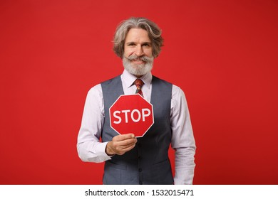 Smiling elderly gray-haired mustache bearded man in classic shirt vest and colorful tie isolated on red wall background. People lifestyle concept. Mock up copy space. Holding red sign with Stop title