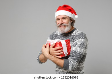 Smiling elderly gray-haired mustache bearded Santa man in sweater Christmas hat isolated on grey background. New Year 2020 celebration holiday concept. Mock up copy space. Hold present box with gift