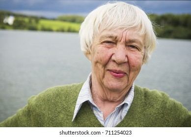 Smiling elderly gray-haired woman outdoors portrait