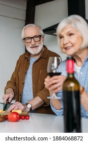 smiling elderly husband looking at wife with wine glass while cooking dinner in kitchen on blurred foreground