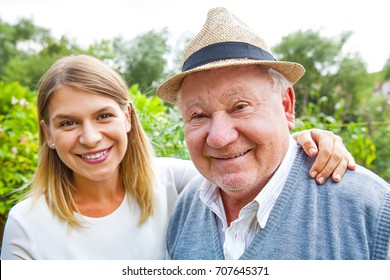 Smiling elderly man with beautiful young granddaughter posing in the park