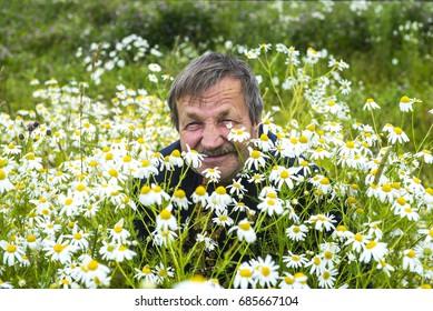 Smiling elderly man in a field among flowers