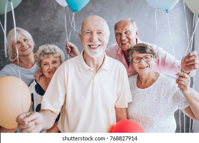 Smiling elderly man and his friends with balloons enjoying his birthday party