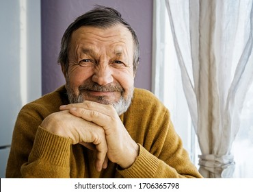 Smiling elderly man at home by the window